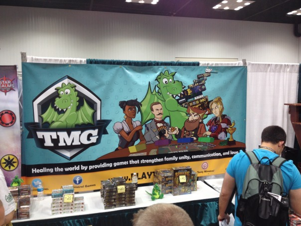 TMG Booth Banner. Check out the awesome game they've got on their table!